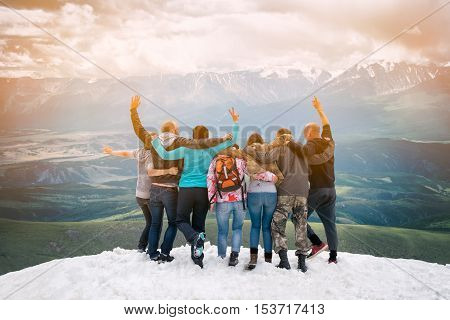 Group of friends are happy that climbed to the top of the mountain. They hug and jump. Looking into the distance with back to the camera.