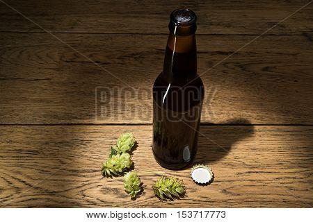 Dark brown beer bottle with raw hops on old wooden table