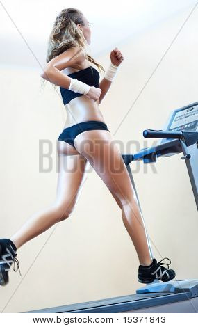 Joven corriendo en la cinta de correr en el gimnasio.