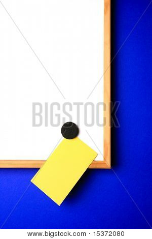 white-board with empty yellow post-it note and magnet