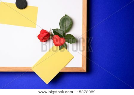 white-board with empty yellow post-it note and magnet in the form of a heart and a red rose