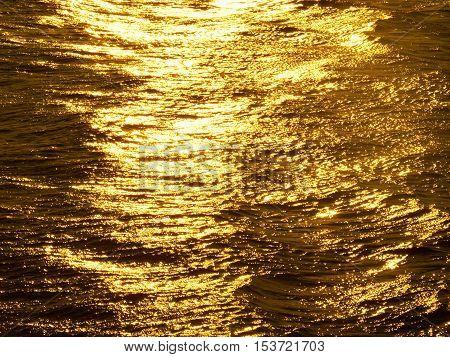 Intensive ripples on sunset water like golden melt.