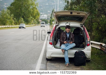 leisure, road trip, travel and people concept - happy man searching location using tablet with online map sitting on trunk of hatchback car outdoors.