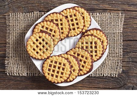Cookies with chocolate in white plate on dark wooden table top view