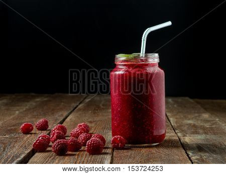 Raspberry smoothie in glass jar with mint straw and berry on dark background