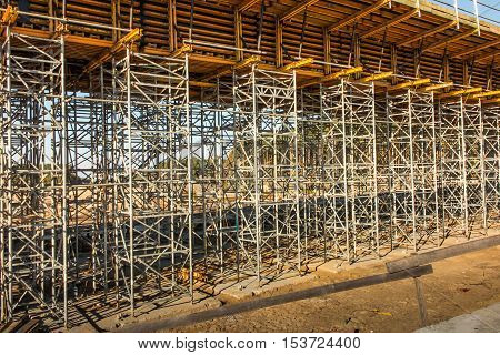 construction scaffolding built under an overpass over the highway as the background