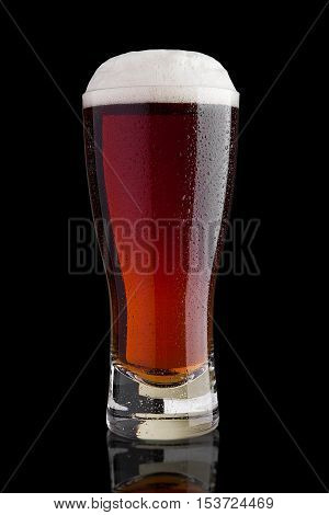 Glass of brown ale beer with foam on black background