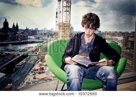 teenager reading a book in a library in front of a window overviewing the city .expressing building his future