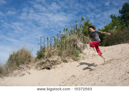 teenager playing at the seaside, running down sand-dunes