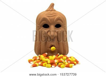 Spooky faced pumpkin surrounded by candy corn with one in its mouth