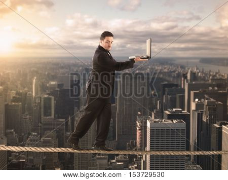 Businessman is balancing on a rope and holds a laptop
