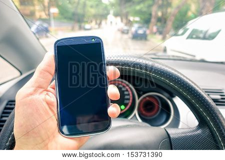 Driver hand holding mobile phone inside car on the road - Close up of smartphone with empty screen to add text or message - Modern concept of dangerous human habits on transport vehicle in daily life