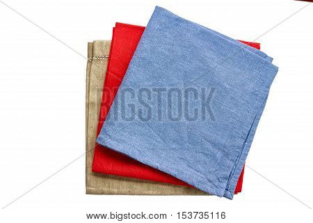 Three colored fabric napkins, blue, red and beige, isolated on white background