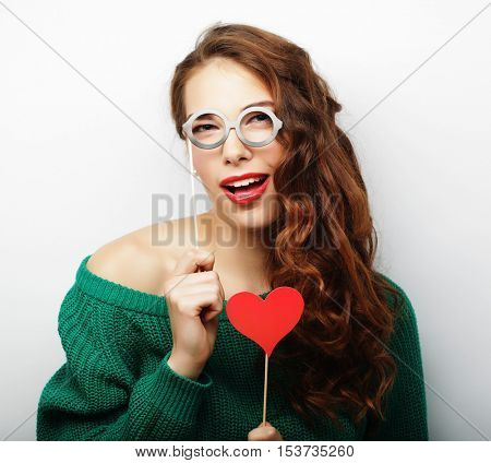 Playful young woman holding a party glasses.