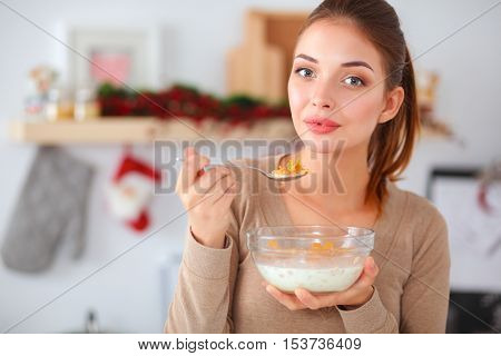 Young smilling woman standing in her kitchen .