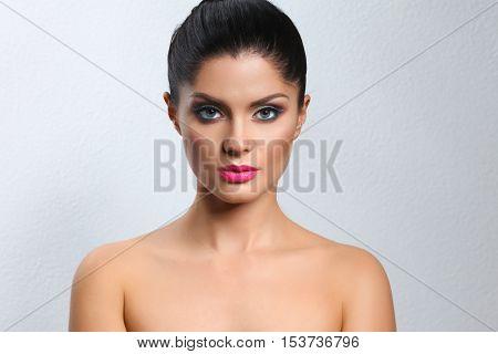Portrait of beautiful woman, on grey background.