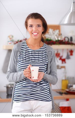 Smiling young woman standing in the kitchen.
