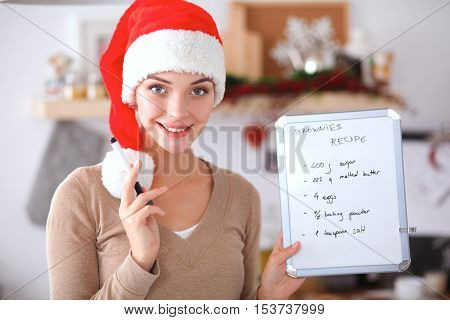Smiling young woman in the kitchen, isolated on christmas background.