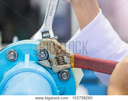 Hand of worker with wrench to tighten nut bolt and pvc pipe