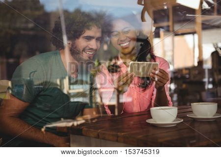Couple looking at mobile phone in cafeteria