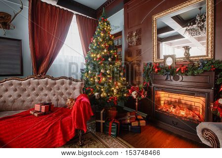 Christmas Eve by candlelight. classic apartments with a white fireplace, decorated tree, sofa, large windows and chandelier