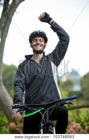 Portrait of excited male cyclist standing with mountain bike in park