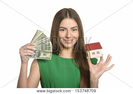 Beautiful woman in green dress with money and little house on white background