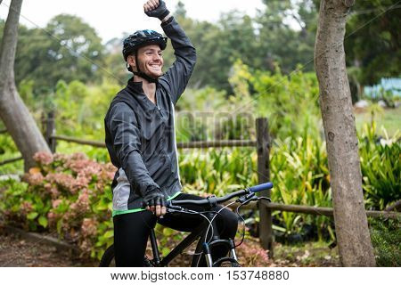 Excited male cyclist standing with mountain bike in park