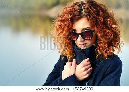 Autumn style. Beautiful young woman with bright foxy hair wearing sunglasses and black coat. Beauty, fashion.
