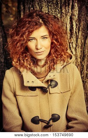 Romantic dreamy girl with beautiful red hair walks in autumn park. The mood of autumn, leaf fall. Autumn fashion.