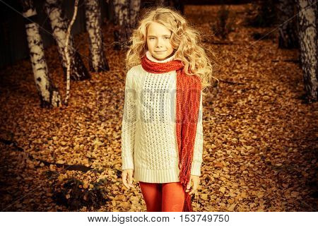 Cute smiling girl walking on a yellow leaves in a beautiful autumn park. Romantic autumn mood. Children's fashion.
