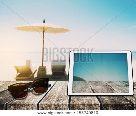 The Beach Holidays, wooden table top, with digital tablet and sun glasses on blurred defocus blue sea and white sand beach in sunrise background