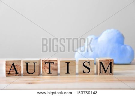 Word autism made of wooden cubes on wall background