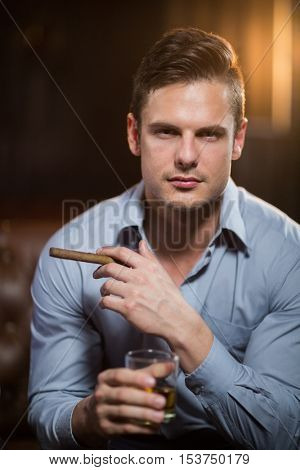 Portrait of man holding a cigar and glass of whisky in bar Portrait of smiling friends holding glass of cocktail in bar