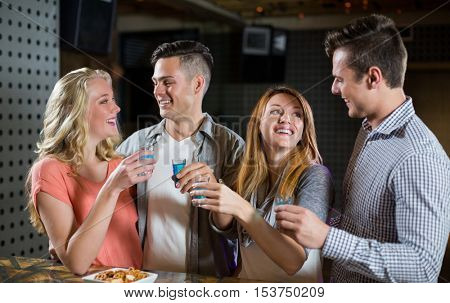 Two smiling couple standing at bar counter and having tequila shots in bar