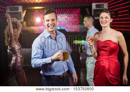 Portrait of smiling couple holding glass of beer and cocktail while dancing at bar
