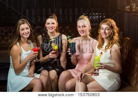 Portrait of smiling female friends holding glasses of cocktail in bar