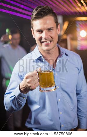 Portrait of smiling man holding glass of beer