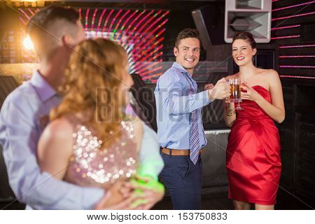 Couple interacting with friends while dancing at bar