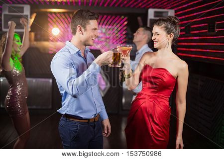 Smiling couple toasting glass of beer and cocktail at bar