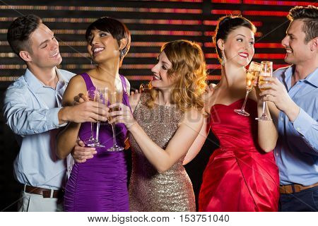 Group of smiling friends toasting glasses of champagne in bar