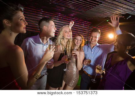 Smiling friends holding glasses of champagne while dancing at bar