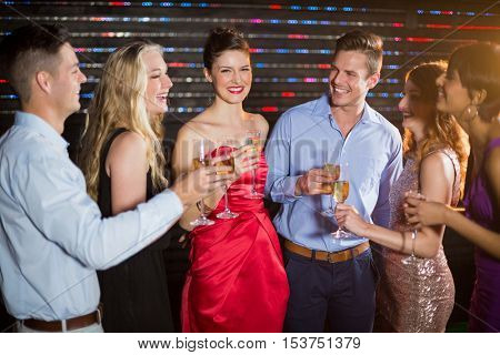 Group of smiling friends having glasses of champagne in bar