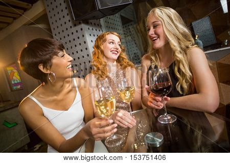 Three smiling friend having glass of champagne at bar