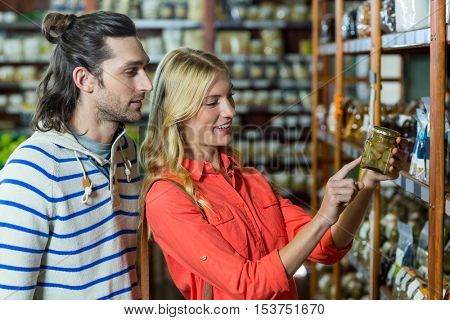 Happy couple selecting pickles in supermarket