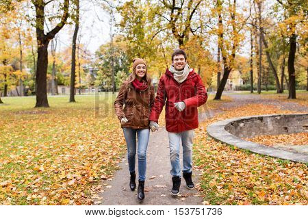love, relationships, season and people concept - happy young couple running in autumn park