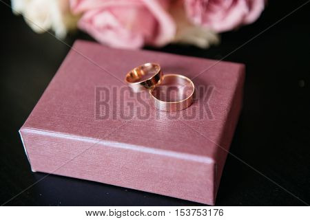 wedding rings pink roses on wooden background