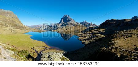 Midi Dossau Peak reflected in Gentau lake. Ossau Valley, Pyrenees National Park, Pyrenees, France.