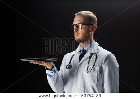 healthcare, people, technology and medicine concept - male doctor in white coat with stethoscope and tablet pc computer over black background