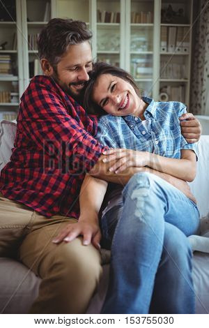 Happy couple embracing on sofa in living room at home
